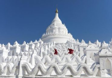 two-young-buddhist-monks-run-and-jump-across-the-white-walls-of-hsinbyume-pagoda-mingun-mandalay_u-l-q1bq34j0